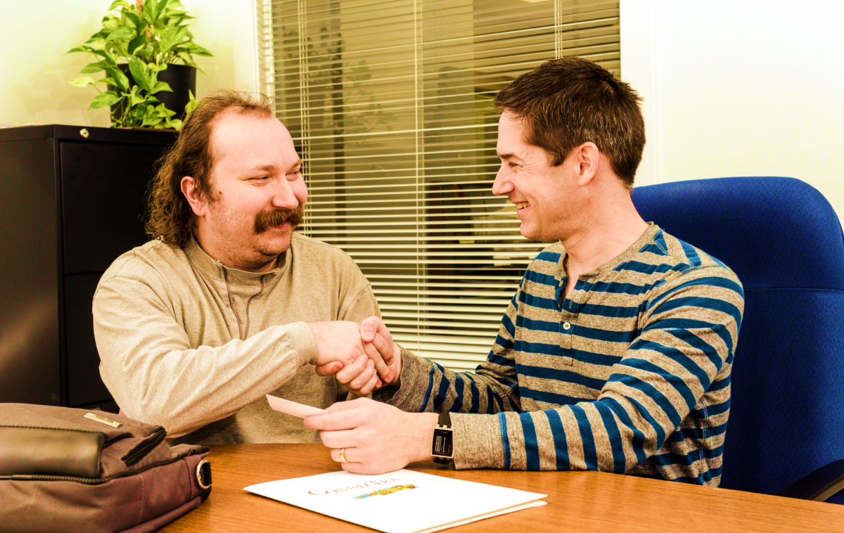 Coworkers smiling and shaking hands.