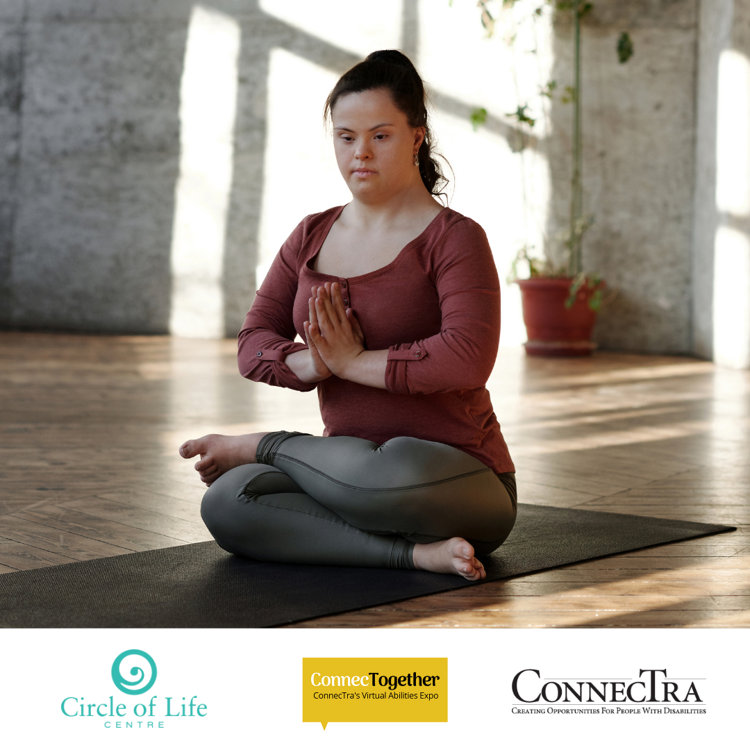 Woman sitting cross legged on the floor meditating.